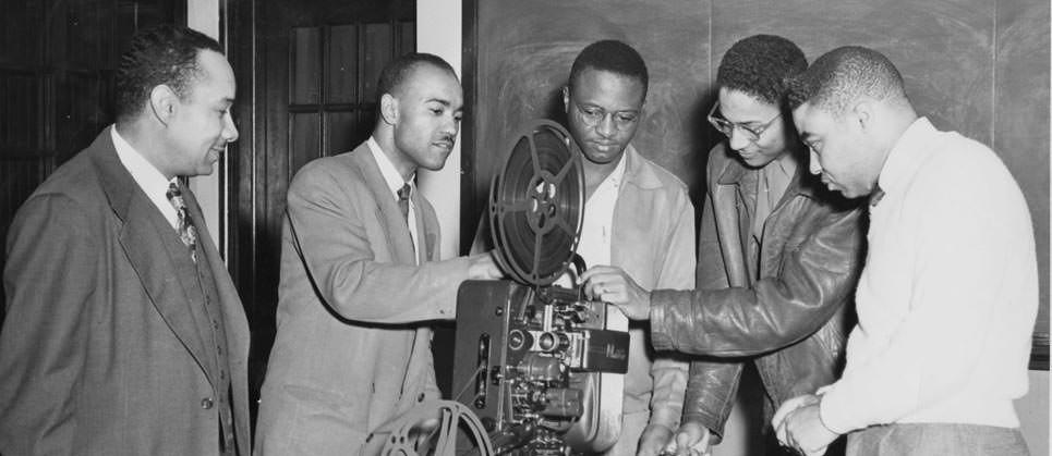 Dr. Richardson & students examine film projector (1955)
