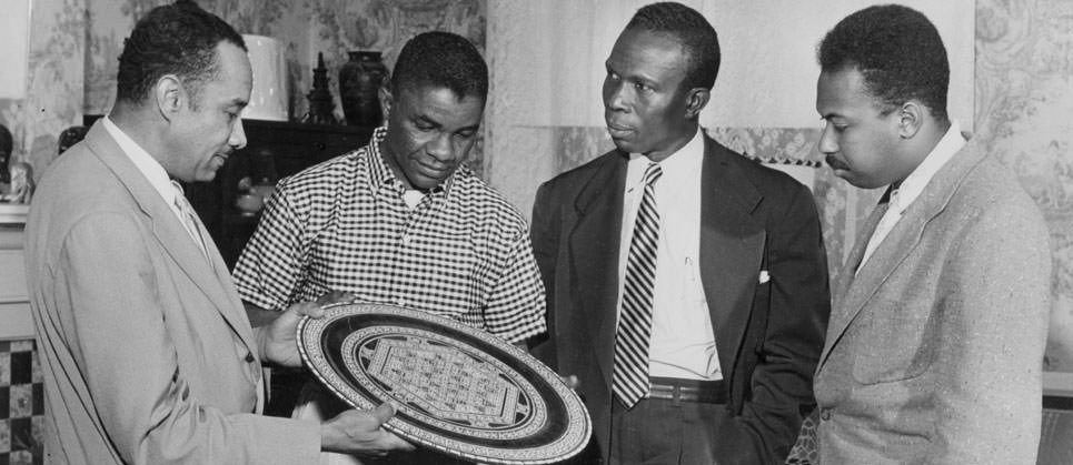 Dr. Richardson showing Afican Plate to three men